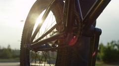 EXTREME CLOSE UP: Sun shining through bmx bike wheel, biker spinning the pedal Stock Footage