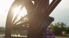 EXTREME CLOSE UP: Details of a bmx bike equipment, sun shining through a wheel Stock Footage