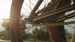 CLOSE UP: Sun shining through bmx bike, biker spinning the wheel and rides away Stock Footage