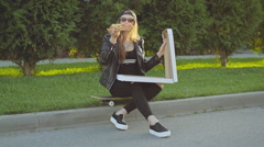 Hipster girl with skateboard an afternoon snack pizza sitting on the sidewalk Stock Footage