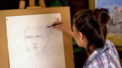 Girl artist paints portrait of woman with pencil. 4k Stock Footage