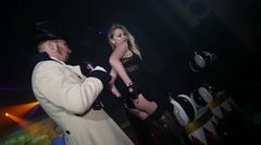 Host in tail coat on stage, girl show underwear at Halloween party. Erotic dance Stock Footage