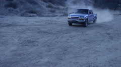 Car taking a turn while passing through a dirt track at dusk Stock Footage