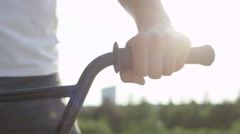 CLOSE UP DOF: Extreme bmx biker holding handlebar grip in sunny evening in city Stock Footage
