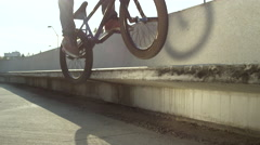 SLOW MOTION CLOSE UP DOF: Extreme bmx biker jumping on bench and sliding on edge Stock Footage