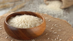 Raw white rice on a burlap rotating. Seamless loopable. 4K Stock Footage
