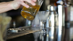 Bartender pouring strong alcoholic drink into small glasses on bar Stock Footage