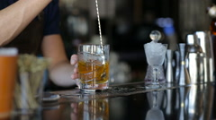 The bartender stirs years and alcohol in a glass Stock Footage