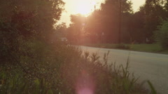 Car passing through a road near forest on a bright sunny day Stock Footage