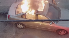 Car burning with large flames and smoke during the day Stock Footage