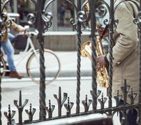 African street musician playing jazz on saxophone throw lattice with bicycle Kuvituskuvat