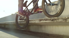 SLOW MOTION CLOSE UP DOF: Extreme bmx biker jumping on bench and peg grinding Stock Footage