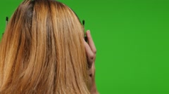 Young female enjoying music on headphones in front of green screen 4K 3840X21 Stock Footage