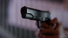 Man's hand shooting with gun at night Stock Footage