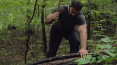 Male Hiker Chopping Stick with Hatchet in Slow Motion Stock Footage