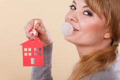 Funny woman holds house keys eat chewing gum Stock Photos