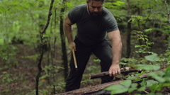 Male Hiker Chopping Stick with Axe in Slow Motion Stock Footage