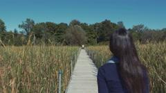 4k - Girl walking near tall grass in a park Stock Footage