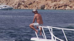 Topless man sitting on nose part of floating yacht. Vacation. Summer sunny day Stock Footage
