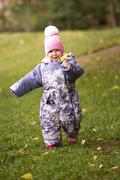 Child - little girl walking in park: baby running at the meadow, close up Stock Photos