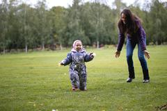 Happy family: Mother and child - little girl walking in autumn park: baby Stock Photos