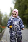 Portrait of child - little girl with fallen leaf walking in autumn park: baby Stock Photos