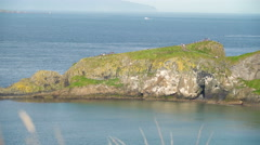 Big rocks on the mountain cliff in Carrick-a-Rede Stock Footage