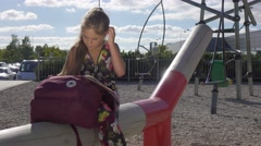 Young girl after school on playground read book  making her homework. Stock Footage