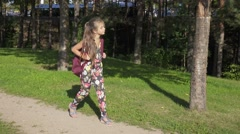 Young nice girl walking through park to school with rucksack, steadicam. Stock Footage