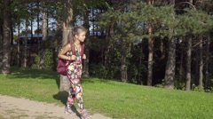 Young nice girl walking through park to school with rucksack, steadicam. Arkistovideo