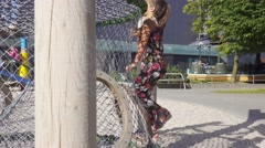 Young girl cilmbs up the net wall on playground, handled camera. Stock Footage