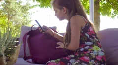 Young girl  sits in street cafe and plays with her smartphone, handled camera. Stock Footage