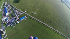 Skydiver girl fly in sky down to green field. Extreme sport. Sunny day. Summer Stock Footage