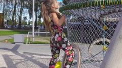 Young girl cilmbs up the net tube on playground, handled camera. Stock Footage