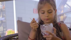 Young girl  sits at table in street cafe and eats ice cream, handled camera. Stock Footage