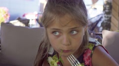 Young girl  sits in street cafe and eats salad and chicken, handled camera. Stock Footage