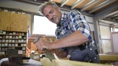 Carpenter working wood in workshop Stock Footage