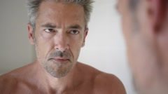 Mature man in front of mirror applying cream Stock Footage