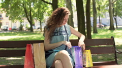 Girl listening music in the park and looking on her shopping Stock Footage