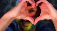 4k Colourful LGBT Shot of a Man in Holy Powder Showing Heart Stock Footage