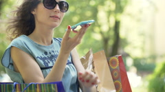 Happy girl talking on loudspeaker while sitting in the park Stock Footage