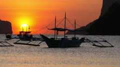 Tropical sunset with a banca boat in El Nido, Palawan, Philippines. Stock Footage