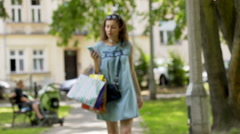 Happy girl walking with shopping bags and listening music on earphones Stock Footage