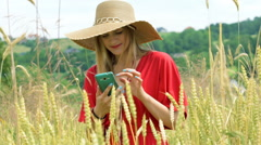 Morose girl standing in the grain field and looking for a signal Stock Footage