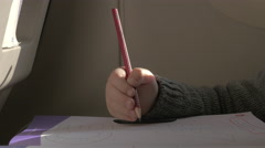 In plane sits a little boy and draws with a pencil on paper Stock Footage