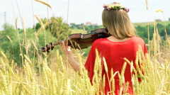 Girl with wreath of flowers standing back and playing violin on the field, stead Stock Footage