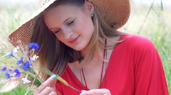 Pretty girl in straw hat holding field flowers and looking thoughtful, steadycam Stock Footage