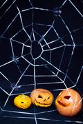 Three Jack O Lanterns behind the spider web against black background Stock Photos