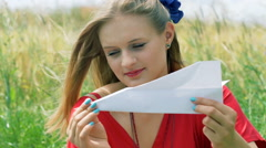 Pretty girl making airplane from a sheet of paper and smiling to the camera Stock Footage