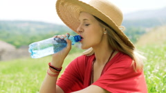 Happy girl sitting on the meadow and drinking water from a bottle Stock Footage